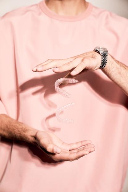 Mann jongliert mit unsichtbaren Zahnschienen, auch Aligner genannt.